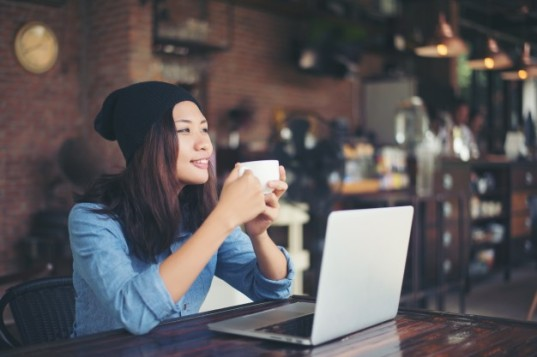 mulher-moderno-bela-jovem-sentada-em-um-cafe-segurando_1150-704